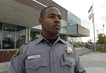 """This photo taken Dec. 8, 2014 shows Alameda County Deputy Sheriff Jorge Ferreira in front of the REACH Crime Prevention unit in San Leandro, Calif. Jorge """"Jinho"""" Ferreira feels the tension between being black and carrying a badge every day as a sheriff's deputy in Alameda County, California. """"I feel like you have to prove yourself on every level,"""" said Ferreira, 39, who patrols about 30 miles east of San Francisco. """"You have to prove yourself to the black community, you have to prove yourself to all of your co-workers, you have to prove yourself to society."""" With the nation roiled by two grand juries' recent refusal to indict white police officers in the deaths of unarmed black men, some black police officers say that as they enforce the law, they also wonder whether the system they're sworn to uphold is stacked against black men. (AP Photo/Ben Margot)"""